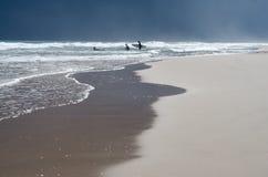 Surfers die het overzees op een bewolkte dag ingaan stock fotografie