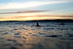Surfers die op Golven als Zonreeksen wachten Stock Foto's