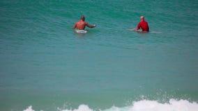 Surfers die op golven wacht stock videobeelden