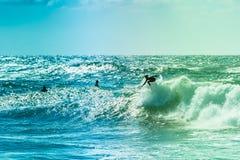 Surfers die sommige golven berijden op het overzees royalty-vrije stock afbeeldingen