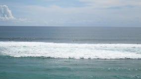 Surfers die tsunamigolven berijden bij Balinees het surfen strand Bali, Indonesië 4K stock videobeelden
