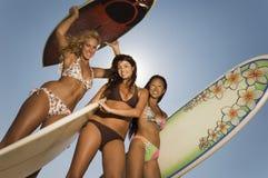 Surfers féminins se tenant avec des planches de surf Image libre de droits