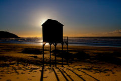 Surfers hut at Sunrise at Kenton on Sea. Life savers and surfers hut on the beach at Kenton on Sea, Eastern Cape Province, South Africa, at sunrise.  The barbed Stock Photos
