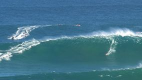 Surfers and jetski at the big wave surfing break jaws at the north shore of the island of Maui, Hawaii