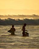 Surfers in Kauai, Hawaii. Surfers enjoying the last hours of the day in Kauai, Hawaii Stock Photos