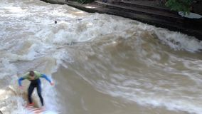Surfers on a man-made wave  on the Eisbach river stock footage
