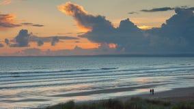Surfers marchant le long et égalisant la plage avec un coucher du soleil derrière eux Image libre de droits