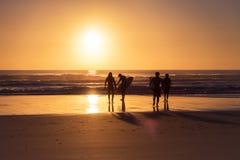 Surfers marchant vers la plage pendant le lever de soleil Photos stock