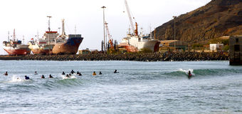 Surfers in the Mindelo bay. Surfers are waiting for the waves in the Mindelo bay in the island of Sao Vincente in  the archipelago of Cape Verde Royalty Free Stock Photography