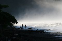 Surfers in the Mist. Two surfers walking on the shore in the early morning mist.  Contrasts between the darkness of night and the lightness of a peaceful morning Royalty Free Stock Images