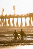 Surfers Near Pier Royalty Free Stock Images