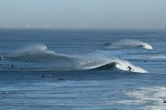 Surfers in the ocean off the coast of Huntington Beach california. With Long Beach in the background Stock Photo