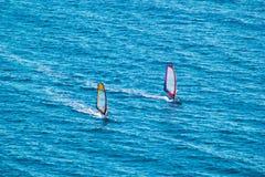 Surfers op blauwe overzees stock foto