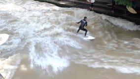 Surfers op een kunstmatige golf op de Eisbach-rivier stock footage