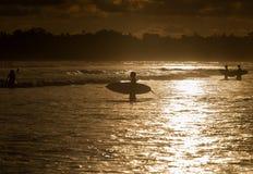 Surfers op het oceaanstrand bij zonsondergang Stock Foto