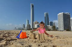 Surfers Paradise Skyline -Queensland Australia. Child (girl age 04) builds sand castle on Surfers Paradise main beach in Gold Coast Queensland, Australia Royalty Free Stock Photo