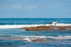 Surfers plongeant outre des roches pour attraper une vague photos libres de droits