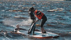 Surfers pushing each other into the water with big soft batons, both falls. Two surfers wearing full swimsuit and life vest pushing each other into the water stock video