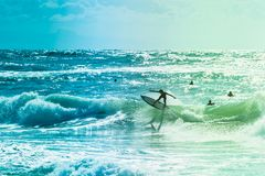 Surfers riding some waves on the sea. Extreme surfers riding some waves on the sea in France Stock Photo