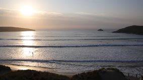 Surfers at sunset Crantock near Newquay Cornwall UK stock video footage