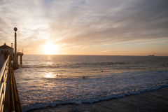 Surfers in the sunset near pier. In California Royalty Free Stock Photo
