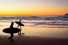 Surfers at sunset, Portugal Stock Photos
