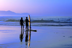 Surfers with sunset reflection on surfboard Stock Image