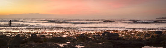 Surfers surf on the waves, bright sunset on the coast, Tenerife, Stock Image