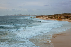 Surfers surf on the waves at Palmahim beach in Israel at sunset Royalty Free Stock Photos