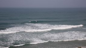 Surfers surfant dans les Cornouailles du nord à la côte cornouaillaise de Porthtowan banque de vidéos