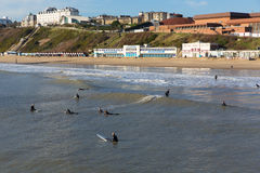 Surfers surfing on Bournemouth beach Dorset England UK near to Poole Royalty Free Stock Image
