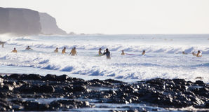 Surfers surfing on El Cotillo beach, Fuerteventura, Canary Islands, Spain. Royalty Free Stock Image