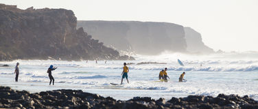 Surfers surfing on El Cotillo beach, Fuerteventura, Canary Islands, Spain. Royalty Free Stock Images
