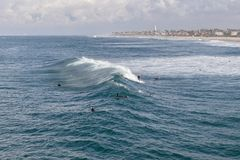 Surfers surfing in the ocean off the coast of Huntington Beach. Surfers catching waves in the ocean with blue sky and water off the coast of Huntington Beach in stock image