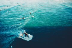 Surfers and swimmers Stock Images
