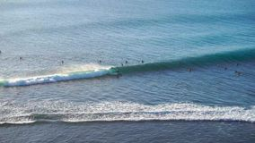 Surfers at Uluwatu blue point surf spot, Bali, Indonesia stock video footage