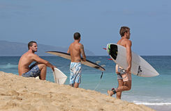 Surfers waiting on beach. For good waves on North Shore of Oahu, Hawaii, holding surfboards Royalty Free Stock Images
