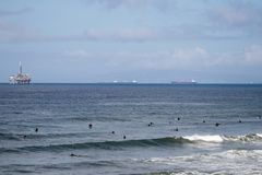 Surfers off the coast of Huntington Beach. Surfers waiting for waves off the coast of Huntington Beach in Orange County california.  Pacific Ocean with Long Royalty Free Stock Photos