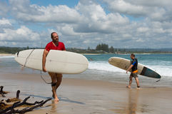 Surfers walk in the beach of Byron Bay. Royalty Free Stock Photos