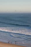 Surfers walking along beach Royalty Free Stock Photo