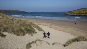 Surfers walking away from camera Crantock bay and beach North Cornwall England UK stock footage