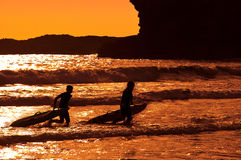 Surfers walking out of the sea Stock Image