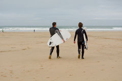 Surfers walking out to sea in British autumnal conditions Stock Image