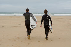 Surfers walking out to sea in British autumnal conditions Royalty Free Stock Images