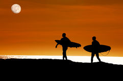 Surfers walking to the ocean for a sunset ride Stock Images