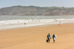 Surfers walking together towards the ocean Stock Image