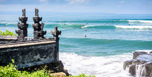 Surfers on a wave by a temple in bali Royalty Free Stock Photo