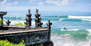 Surfers on a wave by a temple in bali 3 Stock Photo