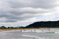 Surfers on Whangamata beach in New Zealand