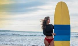 Surfervrouw gaan die status met blauw-gele surfplank op Waikiki-Strand surfen Vrouwelijk bikinimeisje die met surfplank het leven royalty-vrije stock foto's